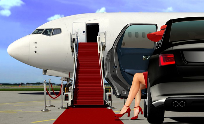 Woman getting out of limo next to a red-carpeted stairway leading to a private plane.