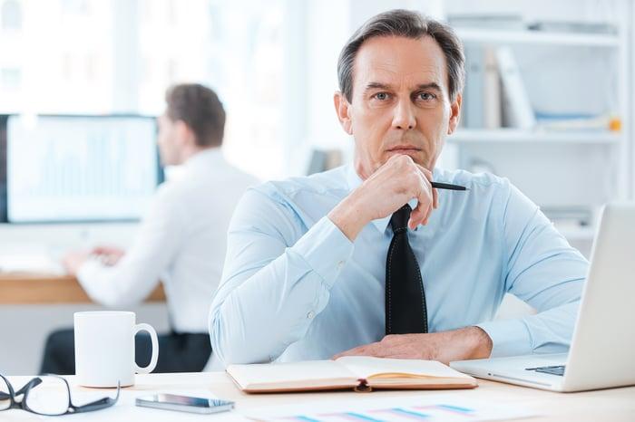 Image shows man sitting at desk