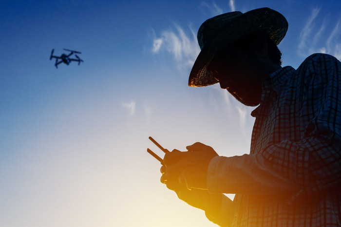 Silhouette of a farmer flying a drone with a remote control
