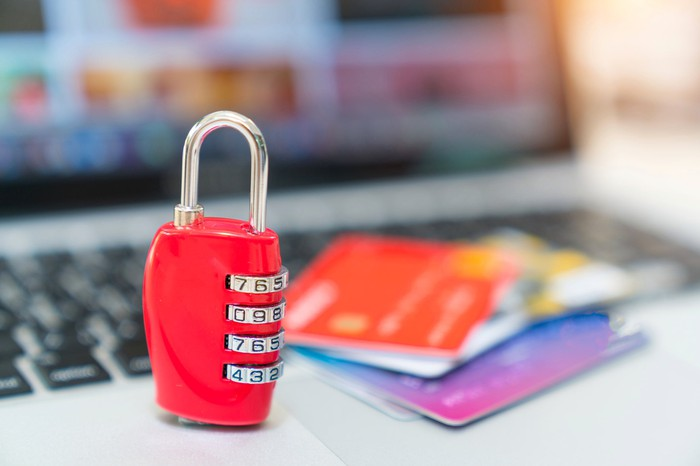 A padlock protects credit cards on a laptop keyboard.