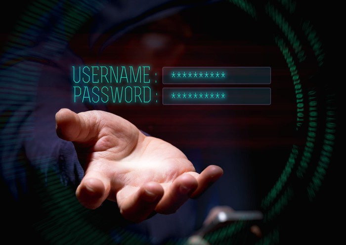 "A hooded hacker reaches toward the words ""username"" and ""password"" on a screen."