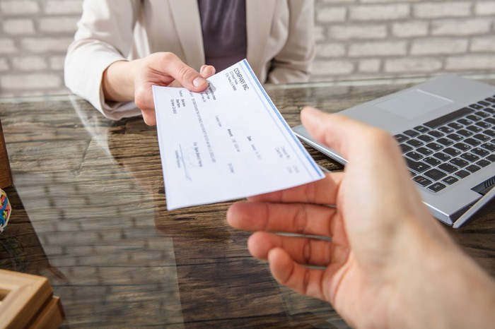 One person hands a dividend check to another.