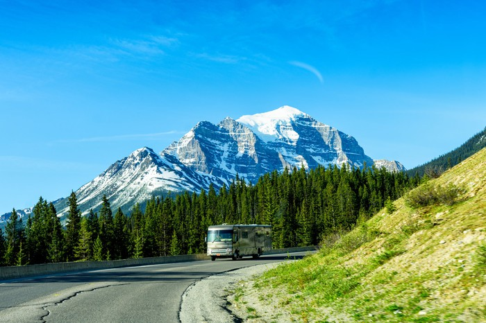 RV driving along curving road with forest and mountains in the background