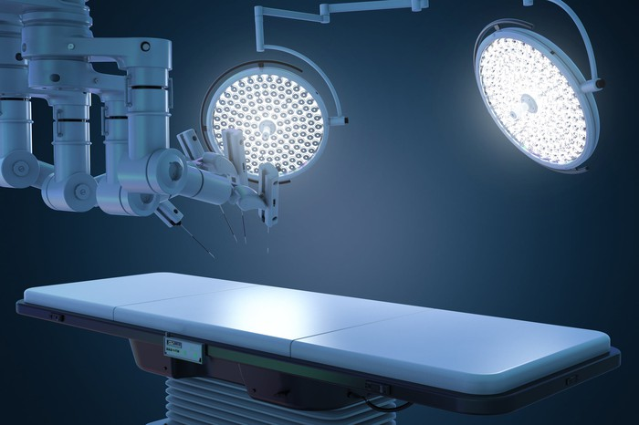 Operating table with two lights above it and a surgical robot