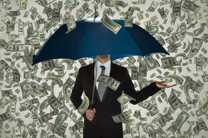 A businessman shelters beneath an umbrella in a shower of hundred-dollar bills.