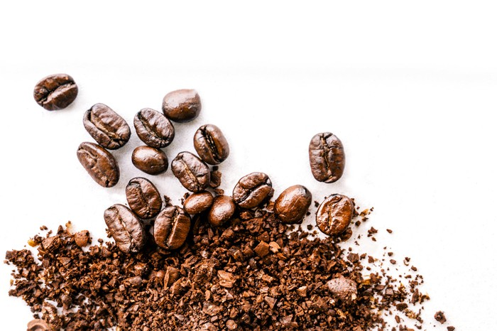 Several coffee beans, with some ground up