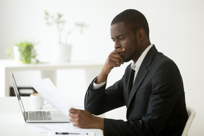A businessman sits at a desk with a laptop and looks at a piece of paper