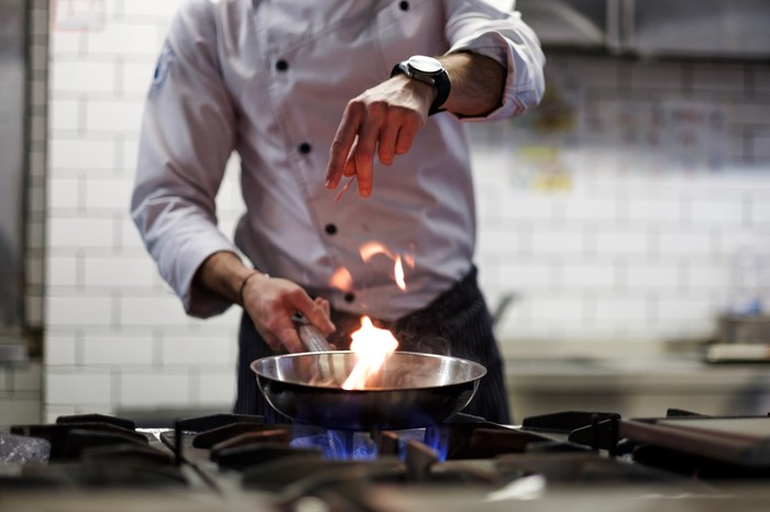 A chef drops ingredients into a saucepan on a stovetop.