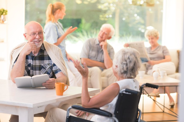 Elderly man talking with woman in wheelchair while sitting together at table in common room in senior living facility