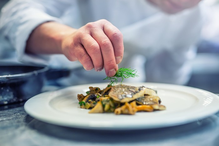 A chef garnishes a plated meal.