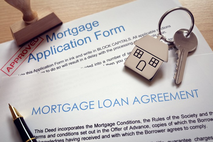A new house key sitting on top of mortgage loan forms.