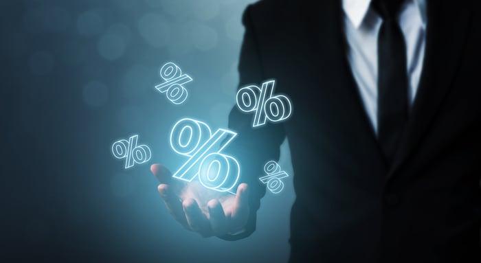 Holographic percentage symbols float above a businessman's hand.