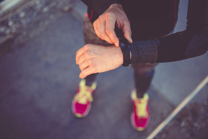 A runner checks the fitness tracker on his wrist.