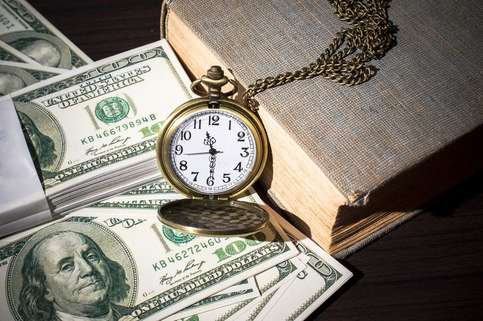 Pocket watch and book next to $100 bills