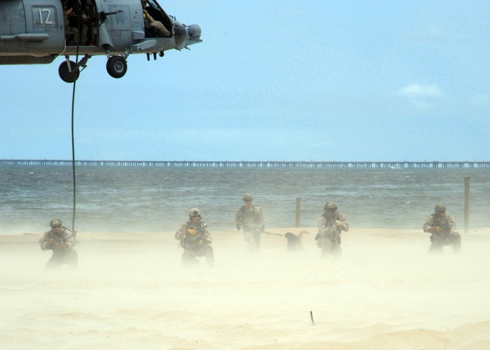 Five Navy seals landing on a beach with a helicopter overhead.