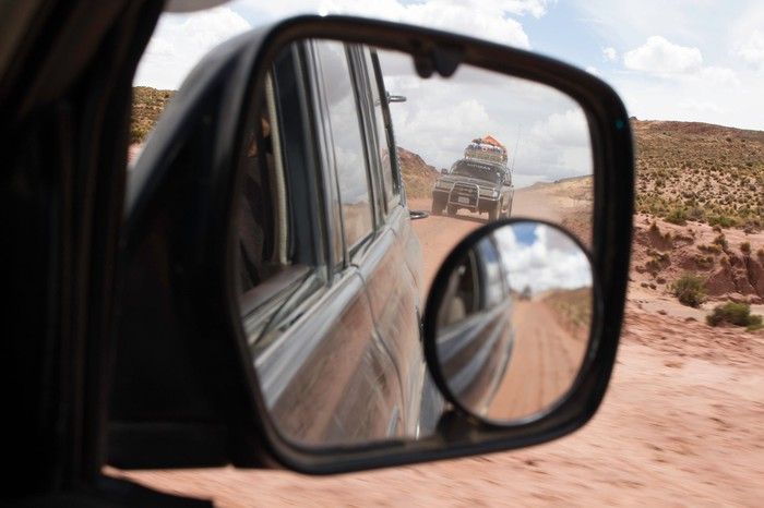 A Land Rover seen in a rear-view mirror.