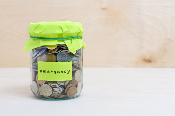"""Jar full of coins with a label that says """"emergency"""" sitting on a white tabletop."""