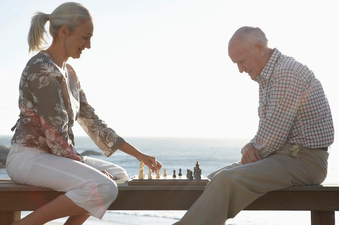 Senior couple playing chess by a beach