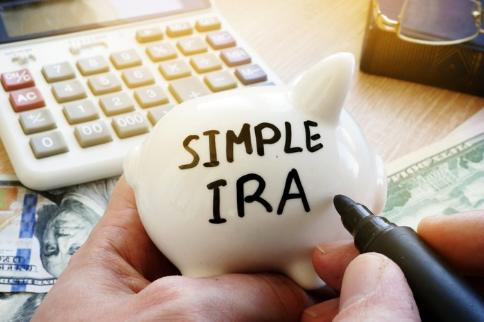 """Someone writing """"SIMPLE IRA"""" on a white piggy bank in front of a calculator"""
