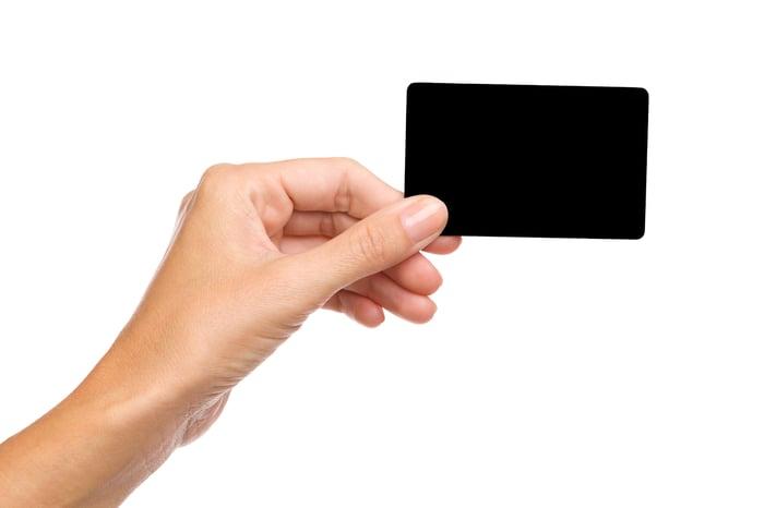 Woman holding black card