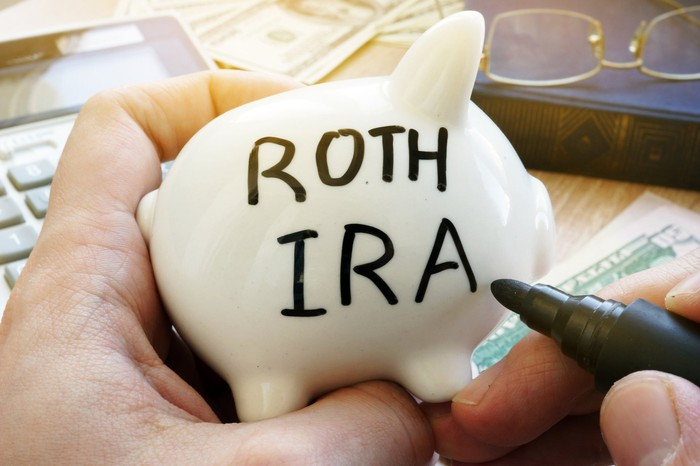 "Hands holding a piggy bank and a market, the piggy bank says ""ROTH IRA"""