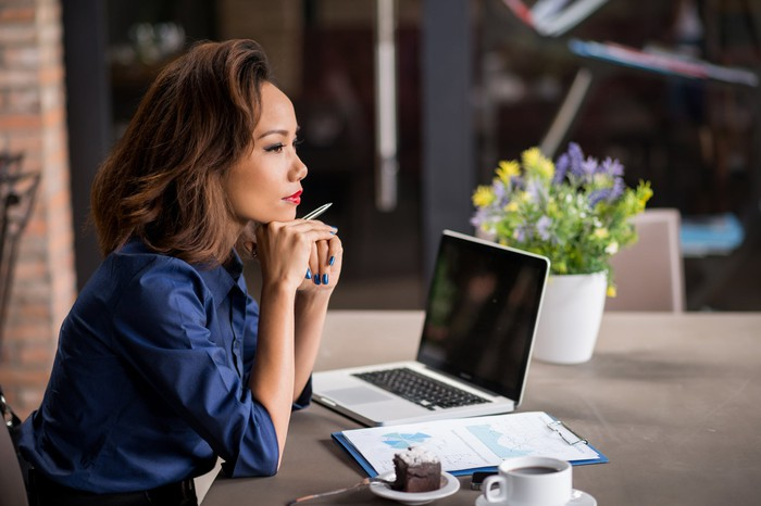 A woman thinking in front of a laptop and some documents