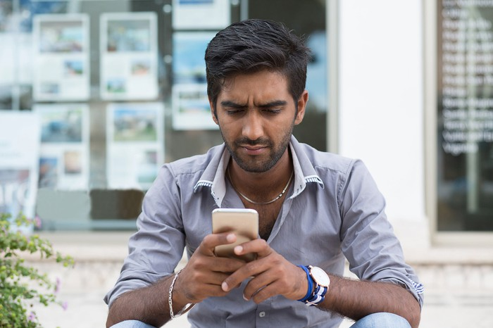 A man sits down and looks at his phone.