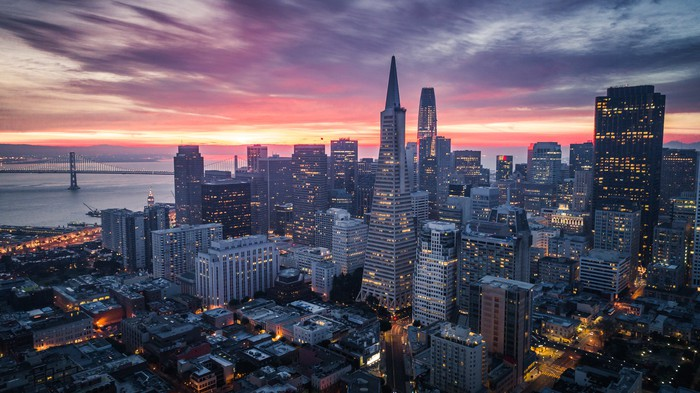 San Francisco skyline at dawn, with a colorful sky