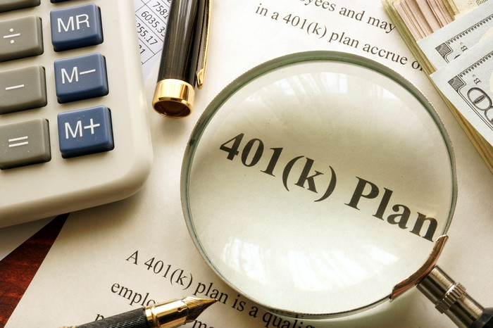 A 401(k) document on a desktop surrounded by a calculator, pen, cash, and magnifying glass.