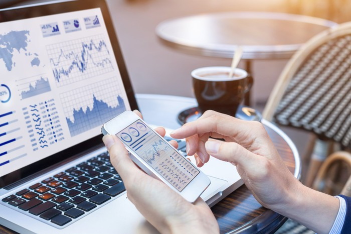 Laptop and smartphone showing stock charts and financial information