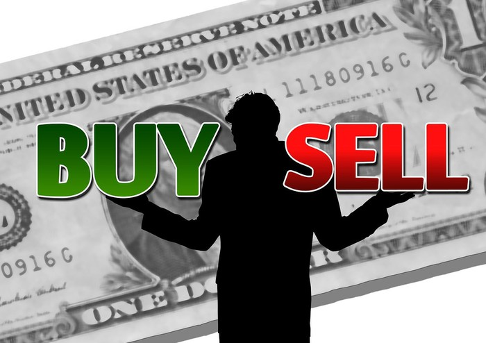 """man in silhouette with arms outstretched, weighing the words """"buy"""" and """"sell"""" and standing in front of a big, projected dollar bill"""