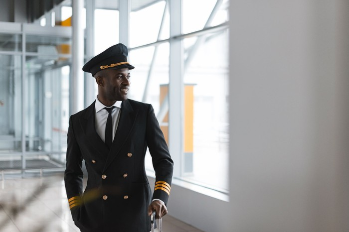 A smiling pilot in an airport concourse.