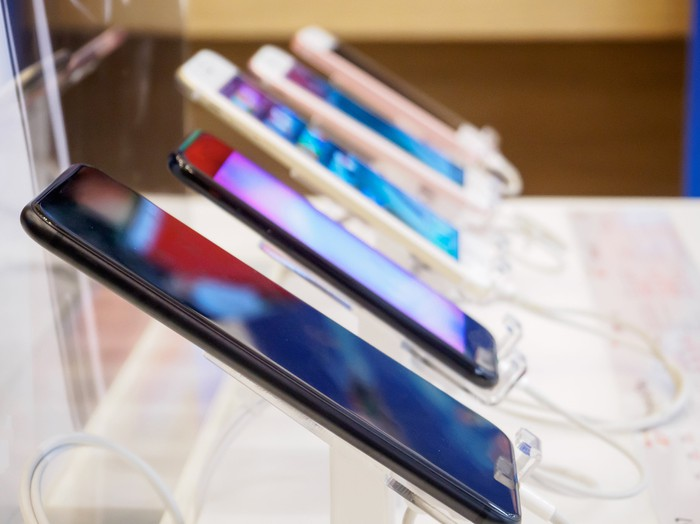 A row of five smartphones on display at a store.