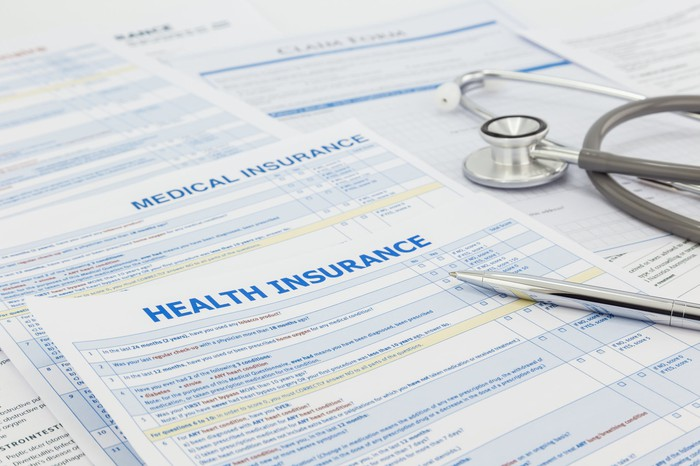 Health insurance forms with a pen and stethoscope on top