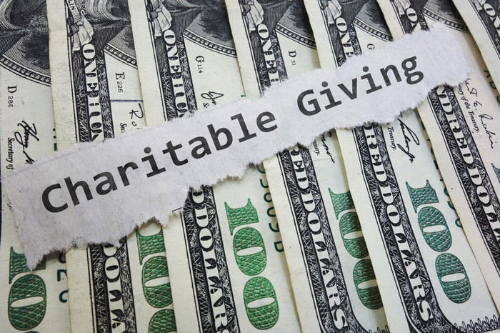 "A piece of paper that says ""Charitable Giving"" sitting on top of $100 bills."