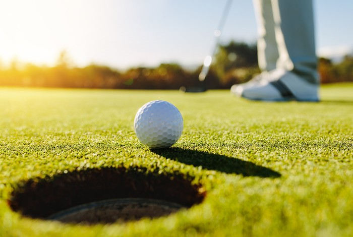 Close-up of golf ball by the edge of hole with player in background on a sunny day