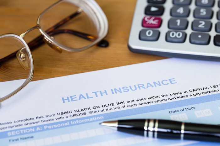 A form that says health insurance under a pen, a calculator, and a pair of glasses.