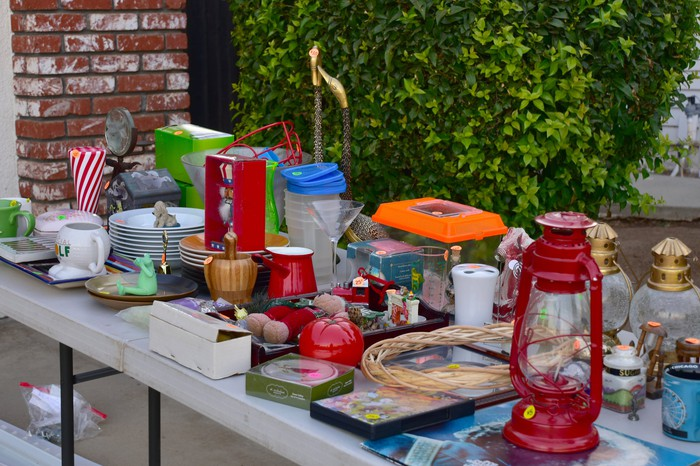 Items lined up on a garage sale table.