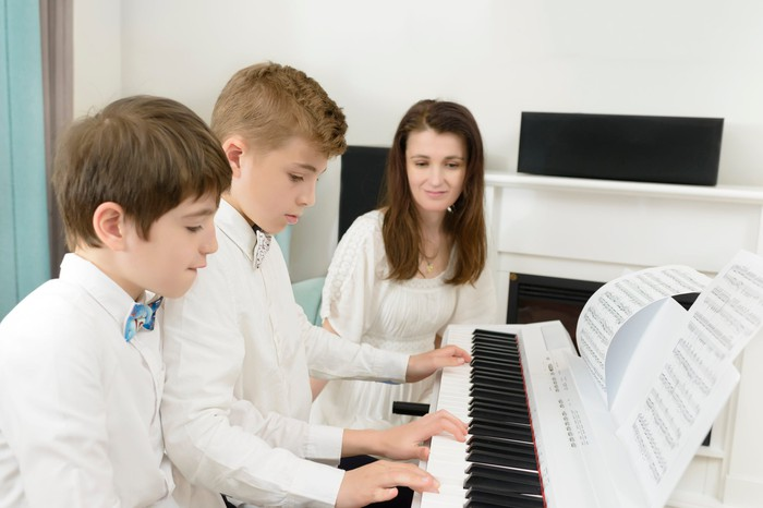 Music teacher teaching two boys how to play the piano.