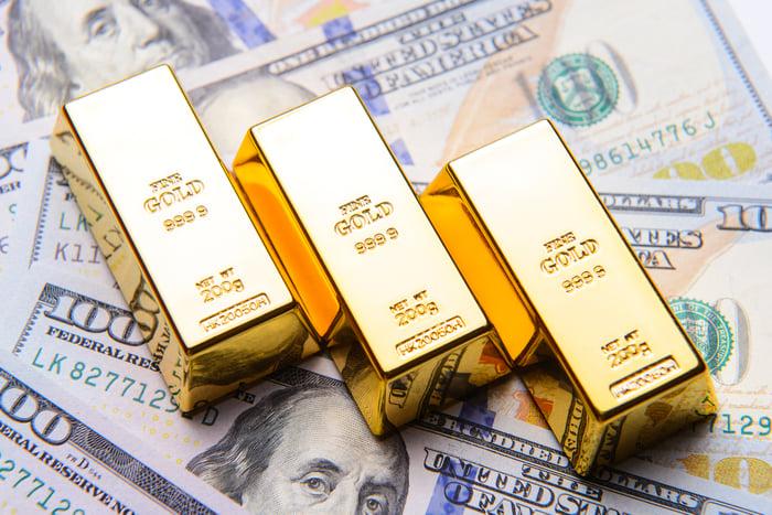 Gold Bars Sitting On Top Of Hundred Dollar Bills