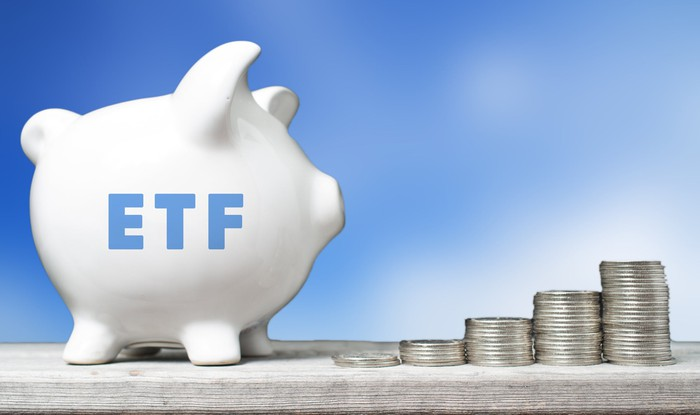 """A piggy bank labelled """"ETF"""" stands next to stacks of coins."""