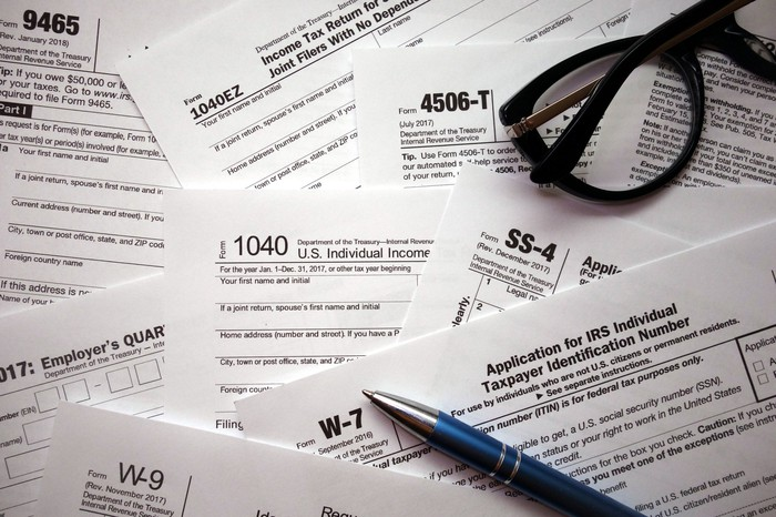 An assortment of tax forms with a pen and a pair of glasses