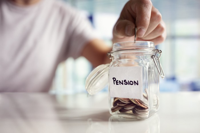 """A hand places coins into a clear jar labeled """"PENSION"""""""