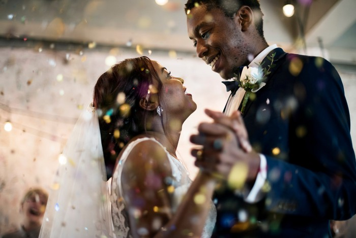 Smiling newlyweds dancing at their wedding reception.