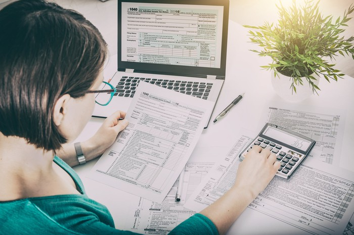 A woman uses a calculator and laptop to figure out her taxes.