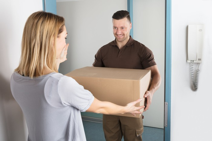 A woman excepting a package from a delivery man.