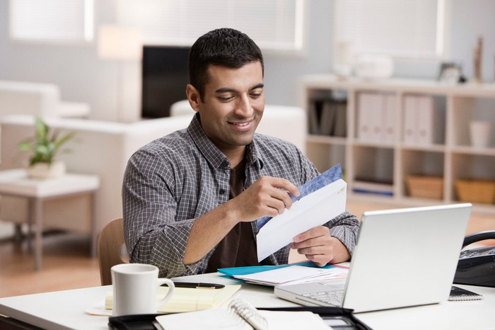 man opening check and smiling