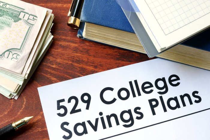 A 529 College Savings Plan document on a desk along with cash and books.
