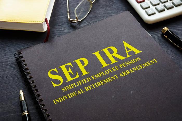"A black binder labeled ""SEP IRA"" sitting on a desk"