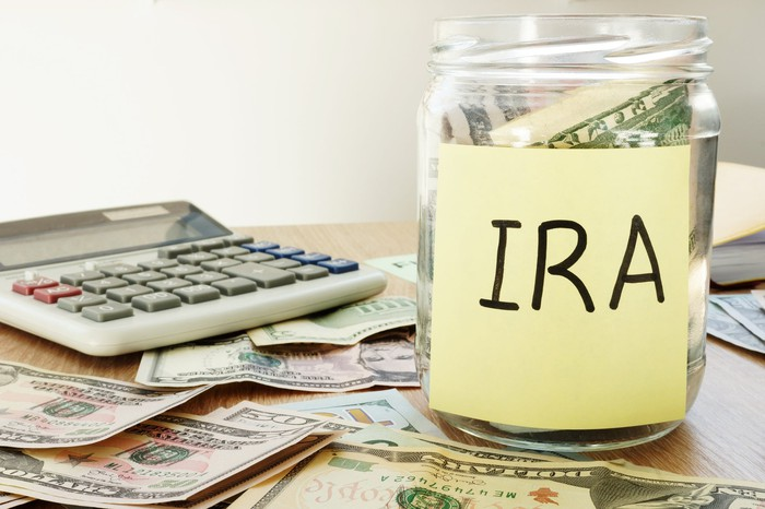 "A clear jar labeled ""IRA"" sitting on a desk covered with money"